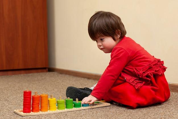 Вид сбоку ребенка с синдромом дауна играет