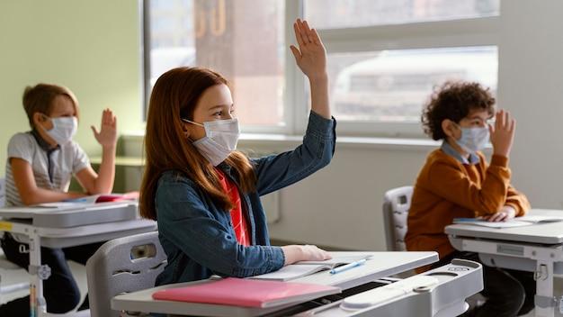 Вид сбоку на детей с медицинскими масками, обучающихся в школе