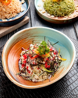 皿に赤キャビアで飾られたキャベツのみじん切りピーマンとシーケールと中華サラダの側面図
