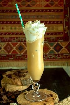 Вид сбоку шоколадный молочный коктейль со взбитыми сливками в высокий стакан на столе