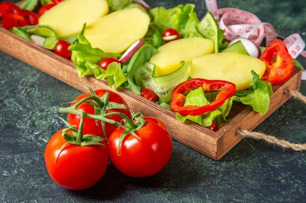 Вид сбоку нарезанных овощей, свежих помидоров со стержневым измерителем на деревянном подносе на поверхности смешанных цветов