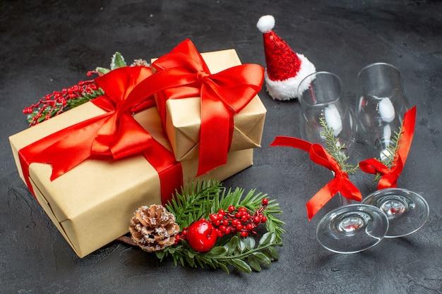 Вид сбоку на новогоднее настроение с красивыми подарками с бантом и украшениями из еловых веток, шапка санта-клауса, упавшие стеклянные бокалы, хвойные шишки на темном фоне