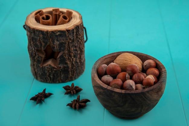 木のボウルと青い背景の上のナッツのボウルのシナモンの側面図