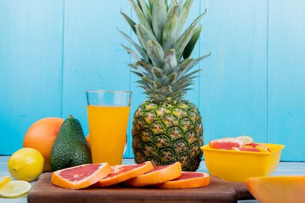 木製の表面と青色の背景にまな板の上のオレンジジュースとスライスしたグレープフルーツとレモンアボカドパイナップルとして柑橘系の果物の側面図