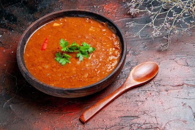 Вид сбоку классического томатного супа в коричневой миске и ложке на столе смешанных цветов