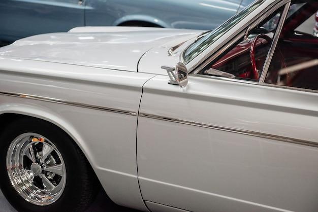 自動車展示会での古典的な白い車の側面図