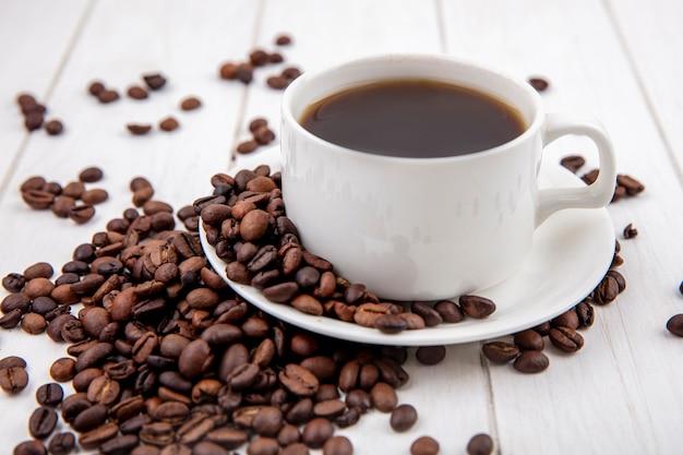 Вид сбоку кофе на белой чашке с кофейными зернами, изолированной на белом деревянном фоне