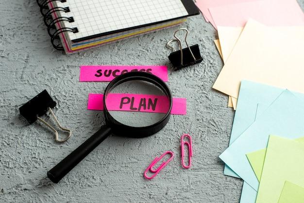 Вид сбоку на цветные конверты и записи плана успеха с увеличительным стеклом и спиральной записной книжкой на фоне серого песка