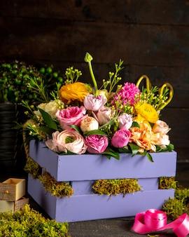 Вид сбоку композиции из розовых и сиреневых роз и цветов лютика в деревянной коробке