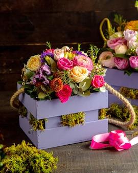 Вид сбоку композиции из розовых кустовых роз и цветов альстромерии с эвкалиптом в деревянной коробке