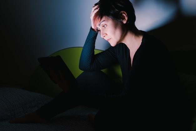 밤에 태블릿 장치 친구를 호출 우려 유럽 여자의 측면보기. 사람들은 새로운 기술에 중독되었습니다. 가정 생활을 유지하십시오.