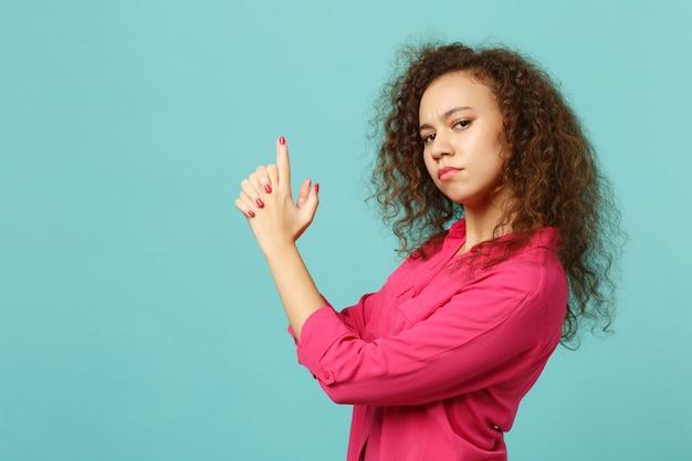 スタジオで青いターコイズブルーの壁の背景に分離された銃のような手を握ってピンクのカジュアルな服を着た自信を持ってアフリカの女の子の側面図。人々の誠実な感情、ライフスタイルのコンセプト。コピースペースをモックアップします。