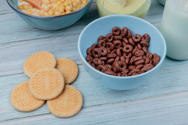 Вид сбоку печенье и крупы в миску с хлопьями для завтрака сгущенное молоко на деревянный стол