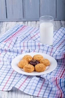 ミルクのガラスを添えて白いプレート上のクッキーの側面図
