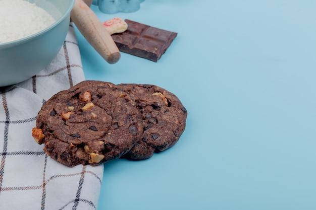 Вид сбоку печенье с мукой шоколада на синей поверхности с копией пространства