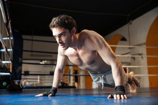 Вид сбоку крутой боксер делает отжимания