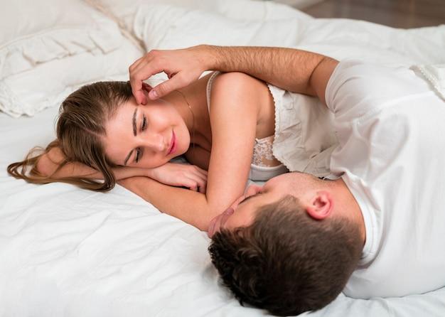 ベッドでロマンチックなカップルの側面図