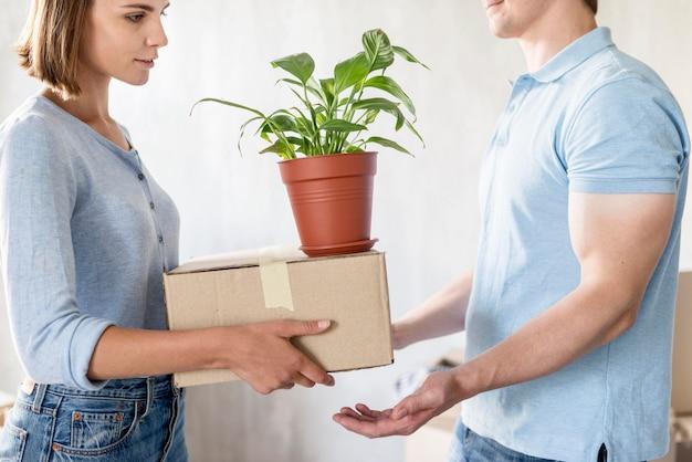 Вид сбоку пары, обрабатывающей коробки и растения во время подготовки к переезду