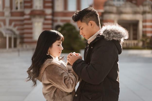 街で屋外で手をつないでいるカップルの側面図