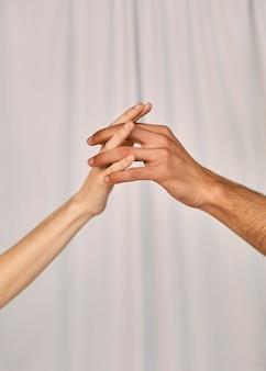Пара, взявшись за руки, вид сбоку