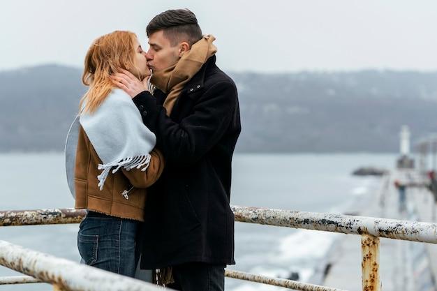 冬の間に湖のそばでキスするカップルの側面図