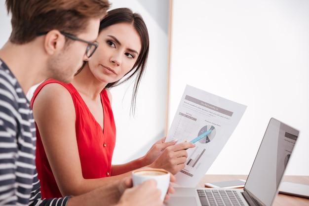 Вид сбоку пара, сидящая за столом с ноутбуком и документами в офисе