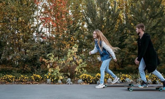 一緒に公園でスケートボードをしているカップルの側面図