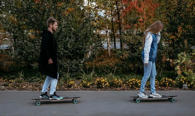 公園でのカップルスケートボードの側面図