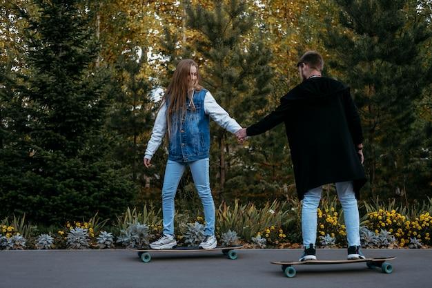 公園で屋外スケートボードのカップルの側面図