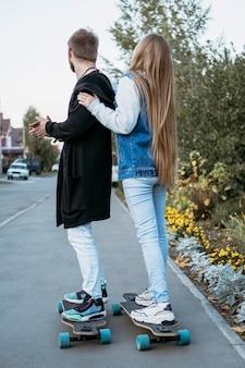 屋外でスケートボードをするカップルの側面図