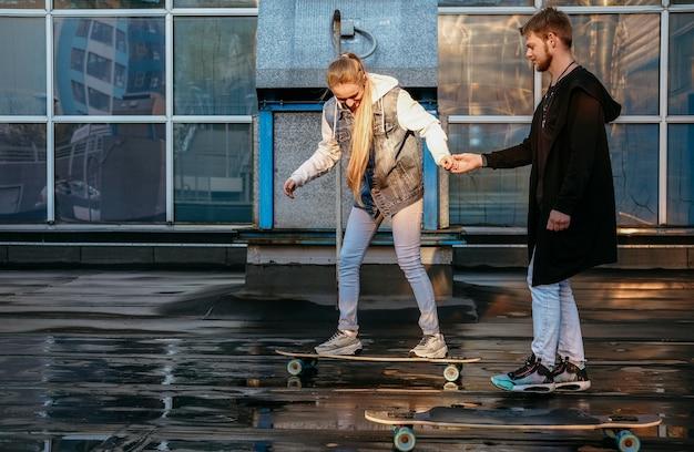 一緒にスケートボードをしているカップルの側面図