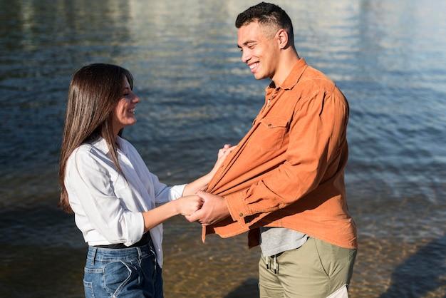 ビーチで一緒に時間を過ごすカップルの側面図