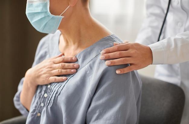 코 비드 회복 센터 여성 의사가 노인 환자를 검사의 측면보기