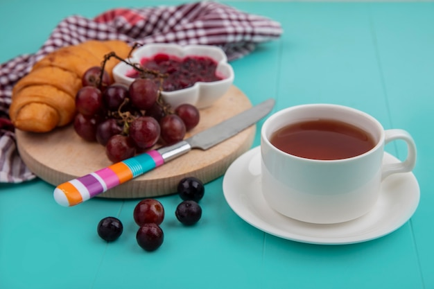 格子縞の布のまな板にナイフと青い背景の上のお茶とクロワッサンとラズベリージャムブドウの側面図