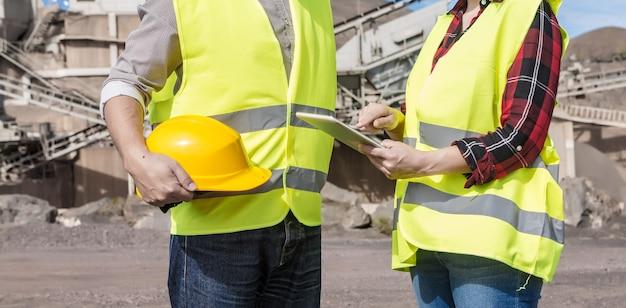태블릿을 사용하고 건설 현장의 산업 시설 근처 남성 동료와 회의 중에 건설 계획을 확인하는 작물 익명 여성 엔지니어의 측면보기