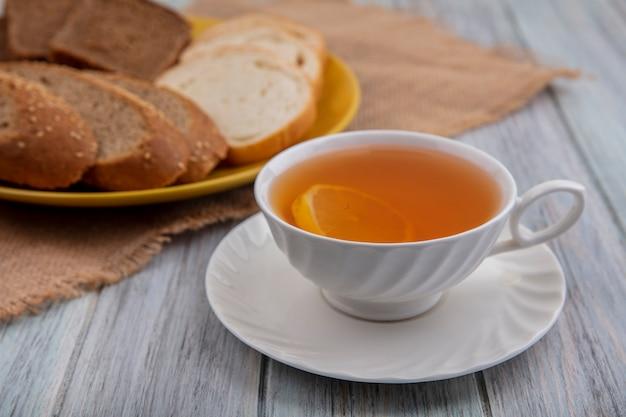 Вид сбоку чашки горячего пунша на блюдце с нарезанным хлебом в тарелке на вретище на деревянном фоне