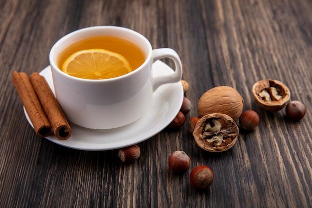 Вид сбоку чашки горячего тодди с корицей на блюдце и орехами грецкими орехами на деревянном фоне