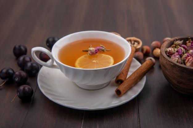 Вид сбоку на чашку горячего тодди с цветком лимона внутри и корицей на блюдце с орехами и грецкими орехами ягод терна и миской цветов на деревянном фоне