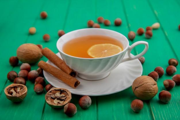 Вид сбоку чашки горячего тодди с лимоном внутри и корицей на блюдце с орехами и грецкими орехами на зеленом фоне