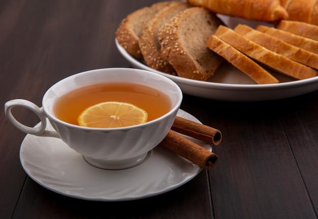 Вид сбоку чашки горячего тодди с лимоном внутри и корицей на блюдце с нарезанным хлебом в тарелке на деревянном фоне