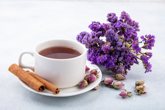 一杯のお茶とシナモンの花とソーサーと白い表面の側面図
