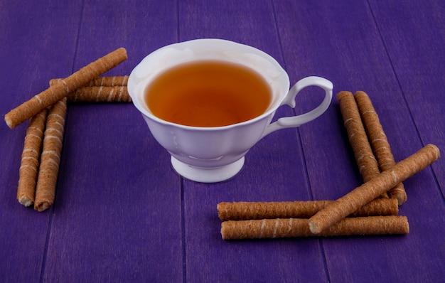 Вид сбоку чашки чая и хрустящих палочек на фиолетовом фоне