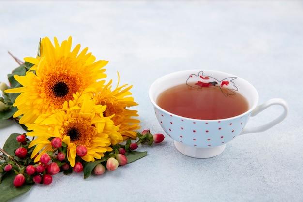 一杯のお茶と白い表面上の花の側面図