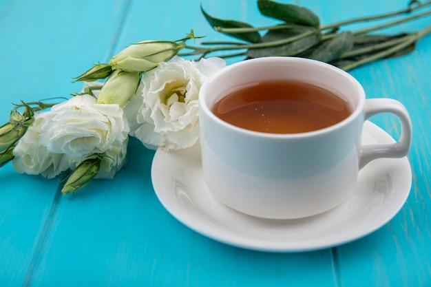 파란색 배경에 접시와 꽃에 차 한잔의 측면보기