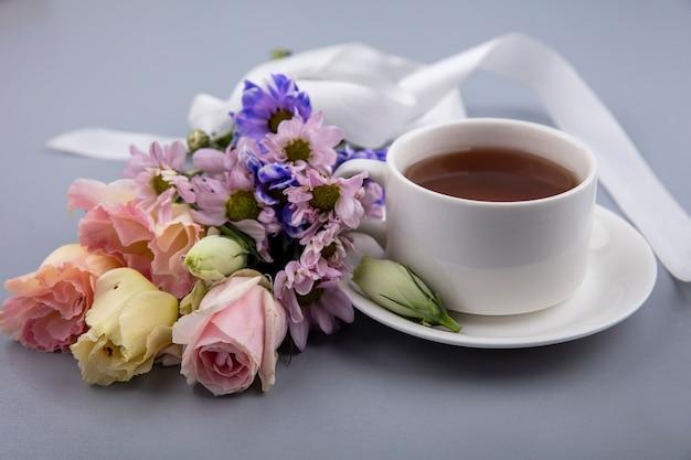 Вид сбоку чашки чая на блюдце и цветы с лентой на сером фоне