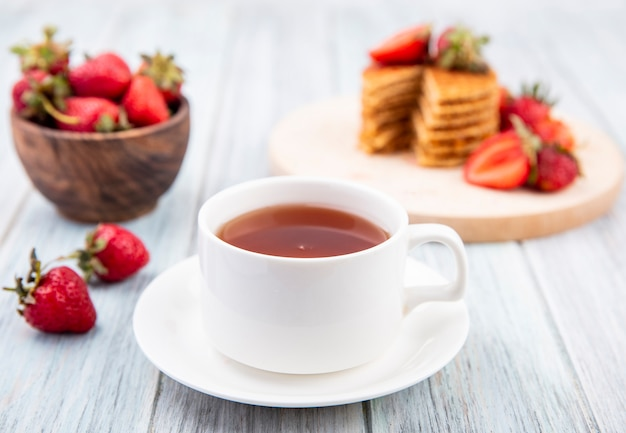 Вид сбоку чашки чая на блюдце и вафельные печенье с клубникой в тарелку и миску на деревянной поверхности
