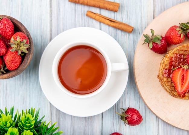 Вид сбоку чашки чая на блюдце и вафельные печенье с клубникой в тарелку и миску с корицей на деревянной поверхности