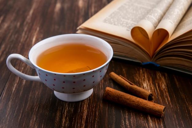 Вид сбоку на чашку чая с корицей и раскрытую книгу на деревянной поверхности