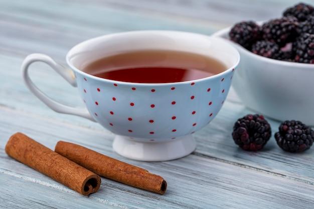 Вид сбоку чашки чая с корицей и ежевикой на серой поверхности