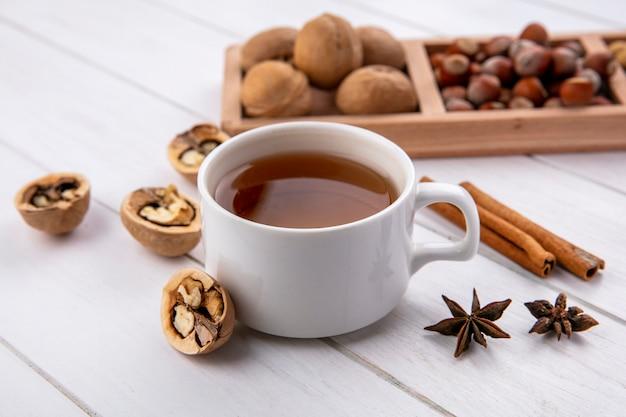 Вид сбоку чашки чая с корицей и орехами на подставке на белой поверхности
